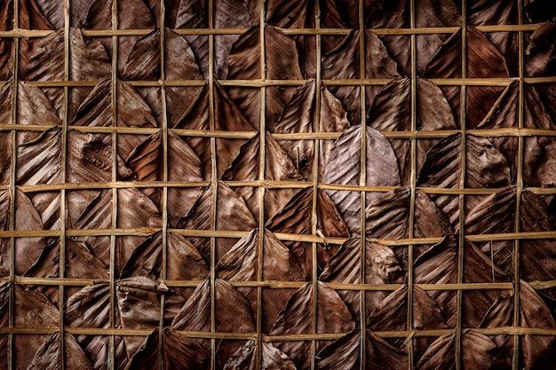 Folhas secas marrons entrelaçam-se nas paredes ou no telhado de uma casa de campo.