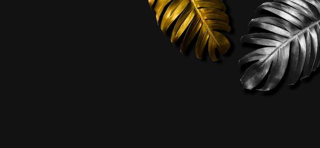 Folhas tropicais de ouro e prata em fundo preto com espaço de cópia