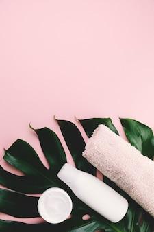 Folhas tropicais de vista superior com ferramentas de beleza e cosméticos