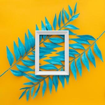 Folhas tropicais exóticas e moldura vazia em amarelo