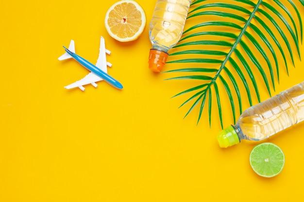 Folhas tropicas e água de garrafa no fundo amarelo. desintoxicação de água com infusão de frutas.