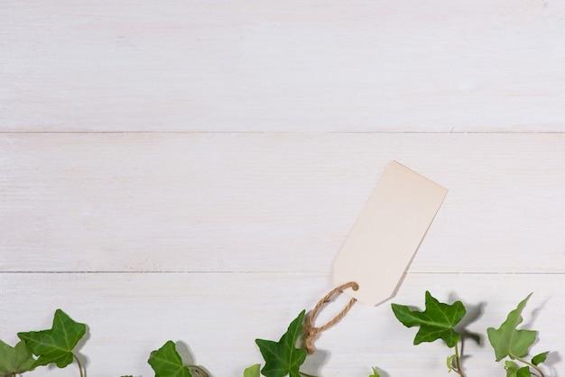 Folhas verdes com etiqueta em branco sobre fundo de madeira