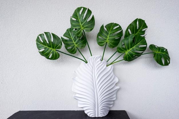 Folhas verdes da planta monstera decoram o interior de um apartamento moderno