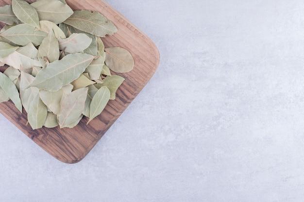 Folhas verdes de louro secas em uma travessa de madeira