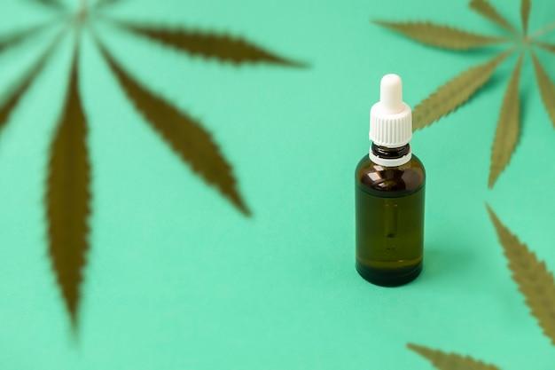 Folhas verdes de maconha em fundo verde com óleo de cannabis em uma garrafa de vidro conceito de cannabis de foco seletivo para fins medicinais