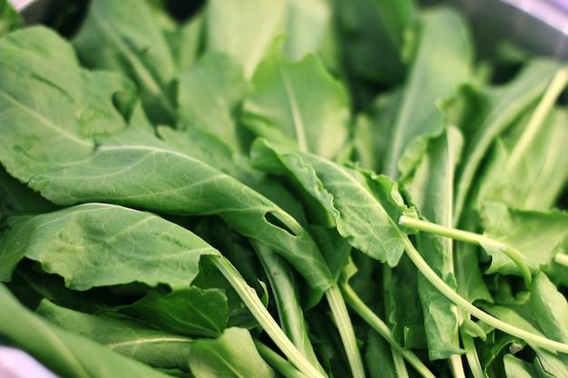 Folhas verdes de rúcula na taça de prata