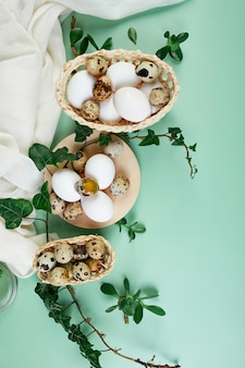 Folhas verdes e ovos de páscoa em uma superfície verde