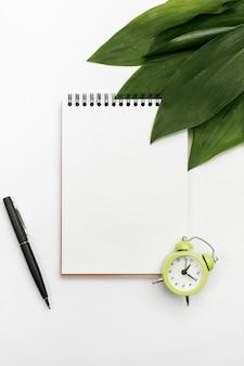 Folhas verdes no bloco de notas em espiral com despertador e caneta em pano de fundo branco