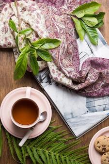 Folhas verdes no livro; xícara de chá e biscoitos na mesa de madeira