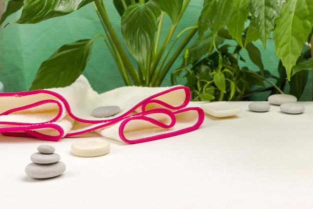 Folhas verdes. pirâmide de equilíbrio de pedra. toalha com borda rosa. conceito de relaxamento do spa. copie o espaço. fundo branco