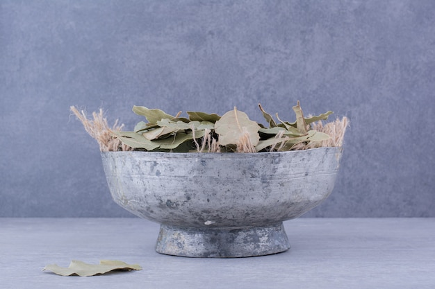 Folhas verdes secas de louro dentro de um recipiente de copo