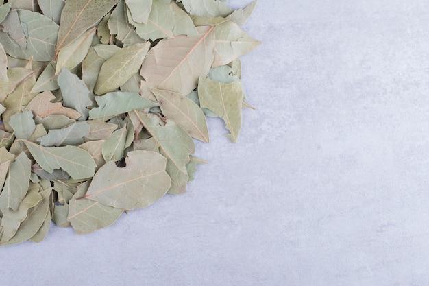 Folhas verdes secas de louro em uma superfície de concreto