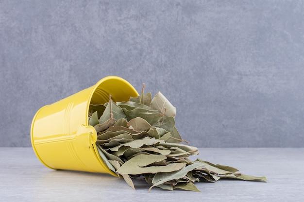 Folhas verdes secas de louro em uma xícara na superfície de concreto