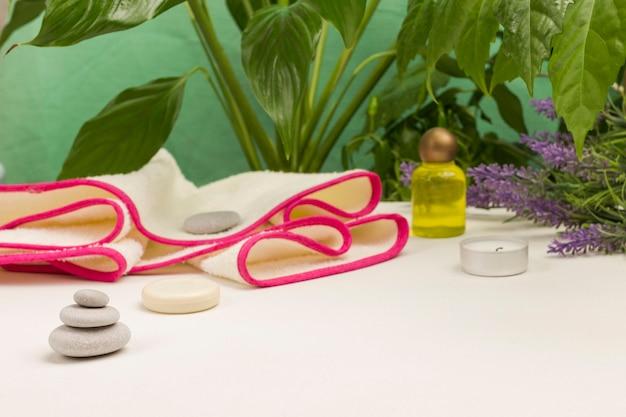 Folhas verdes, velas. pirâmide de equilíbrio de pedra. conceito de relaxamento do spa. copie o espaço. fundo branco