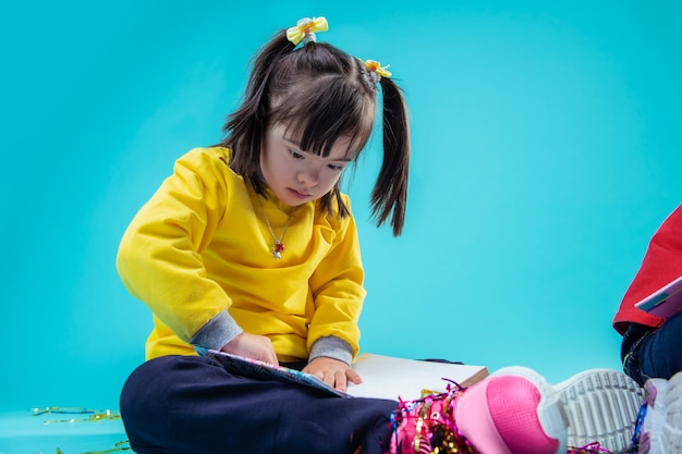 Folheando o livro. menina atenciosa interessada se educando com o livro enquanto o carrega sobre os joelhos