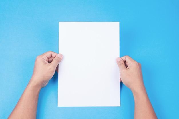 Folheto em branco com placa na mão no fundo azul. maquete para design