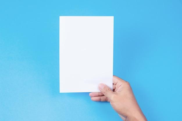 Folheto em branco com placa na mão no fundo azul.