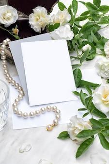 Folheto ou cartão de convite de pôster de maquete com rosas brancas sobre fundo de mármore e colar de pérolas com caixa de joias de prata papelaria para casamento vista superior