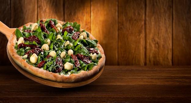 Folheto promocional de conceito e pôster para restaurantes ou pizzarias, template com deliciosa pizza, tomate seco, rúcula e cogumelos, queijo mussarela.