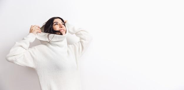 Folheto. retrato de uma linda mulher morena com manga comprida macia confortável isolado no fundo branco do estúdio. conforto doméstico, emoções, expressão facial, conceito de clima de inverno. copyspace.