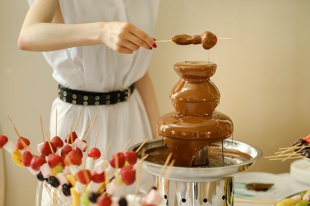 Fondue com fonte de chocolate e doces. tema doce