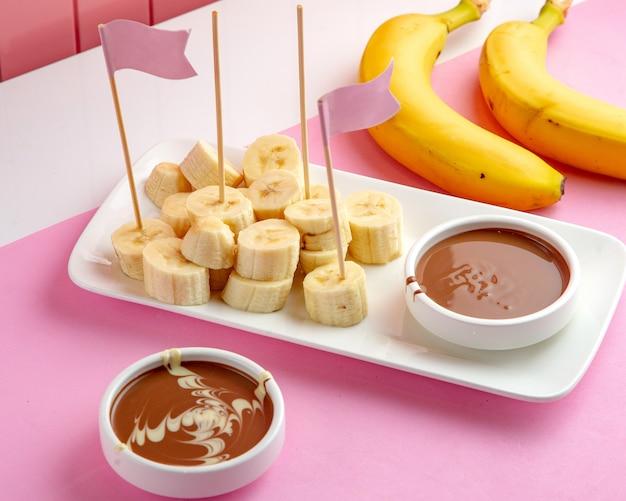 Fondue de bananchocolate com banan e chocolate derretido na mesa