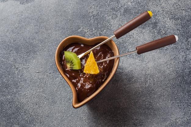 Fondue de chocolate com frutas em um concreto escuro