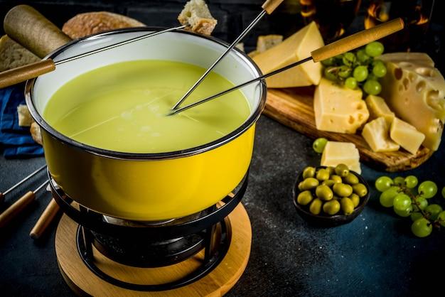Fondue suíço gourmet em panela de fondue tradicional, com garfos, queijos diversos, azeitonas, pão e uva