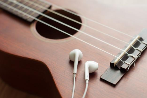 Fone de ouvido branco no ukulele