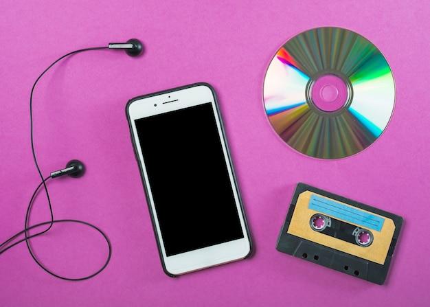 Fone de ouvido; celular; disco compacto e fita cassete no fundo roxo