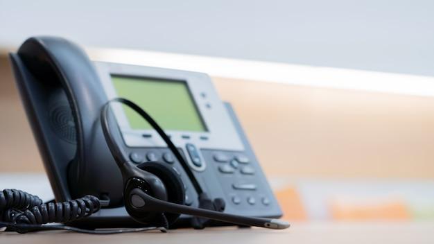 Fone de ouvido com dispositivos de telefone na mesa de escritório para o conceito de suporte de serviço ao cliente