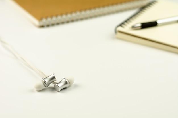 Fone de ouvido com livro diário e caneta sobre fundo branco de mesa.