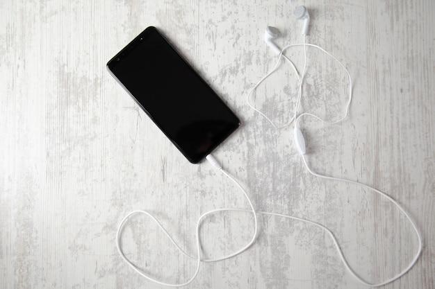 Fone de ouvido com telefone inteligente no fundo da mesa