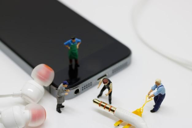 Fone de ouvido de movimento de trabalhador em miniatura para o telefone.