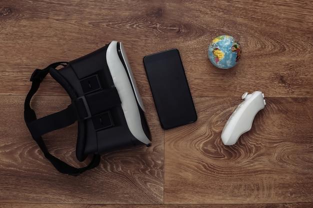 Fone de ouvido de realidade virtual com joystick e smartphone, globo em fundo de madeira. viagem virtual.