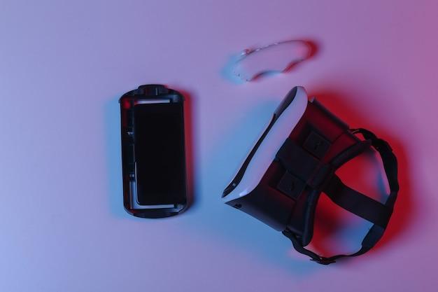 Fone de ouvido de realidade virtual, smartphone e joystick em luz de néon gradiente azul vermelha. vista do topo