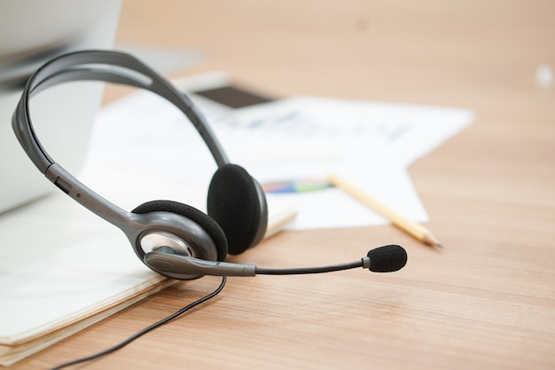 Fone de ouvido do call center na sala de escritório do computador com o conceito de relatório financeiro.