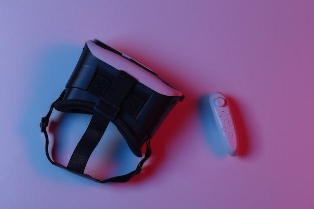 Fone de ouvido e joystick de realidade virtual em luz de néon gradiente azul vermelha. vista do topo