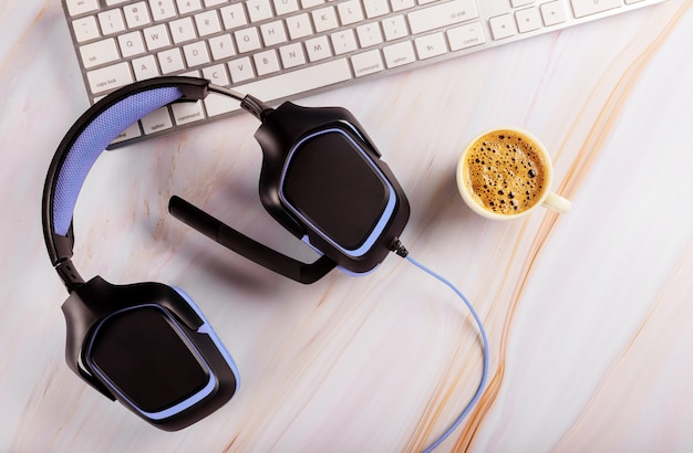 Fone de ouvido em cima da mesa pelo teclado no call center e serviço de suporte técnico na xícara de café