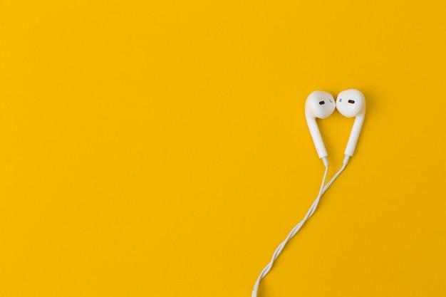 Fone de ouvido em fundo amarelo.