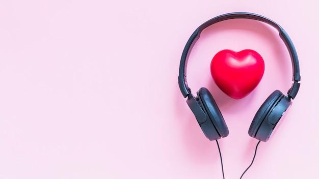 Fone de ouvido em torno da forma de coração vermelho contra o pano de fundo rosa