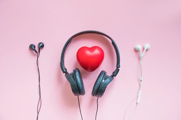Fone de ouvido em torno do coração vermelho entre dois fones de ouvido contra o pano de fundo rosa