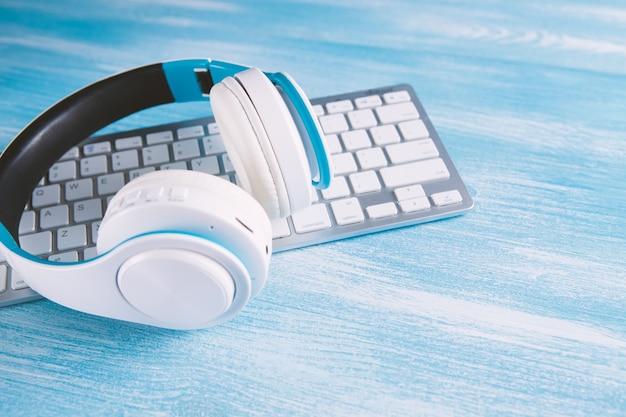 Fone de ouvido em um laptop keywhite fones de ouvido com computador ouvindo audiolivro ou musicboard.