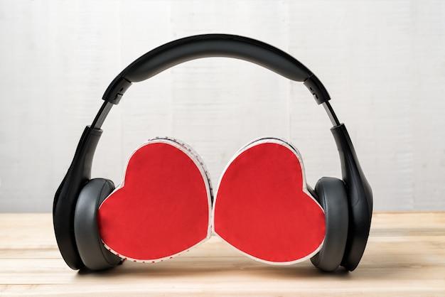 Fone de ouvido estéreo sem fio e duas caixas em forma de coração. ouça o seu coração