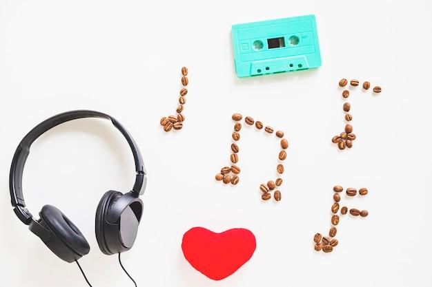 Fone de ouvido; formato de coração; cassete turquesa e grãos de café sobre branco
