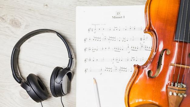 Fone de ouvido; lápis; e violino sobre nota musical em fundo de madeira