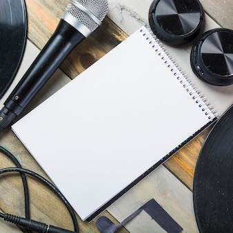 Fone de ouvido; microfone; disco de vinil e bloco de notas em branco em espiral na mesa de madeira