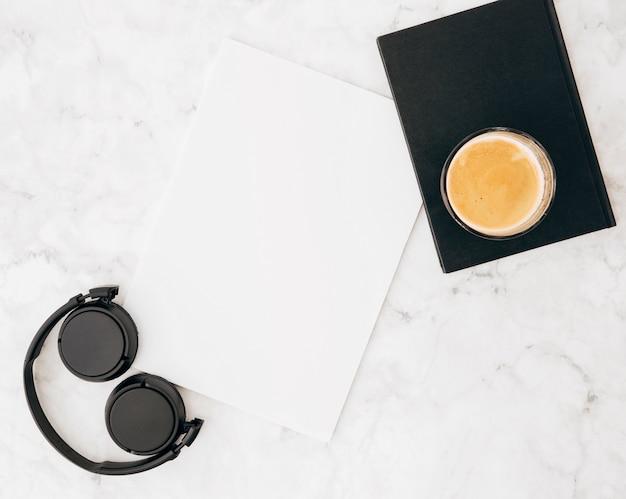 Fone de ouvido; papel em branco; diário e copo de café em mármore texturizado sobre fundo branco