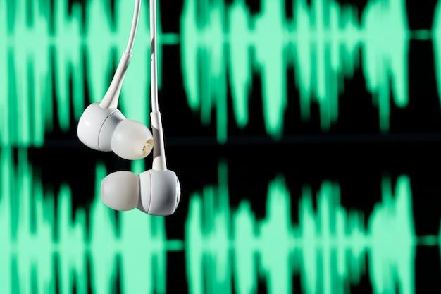 Fone de ouvido pendurado com ondas sonoras no fundo desfocado