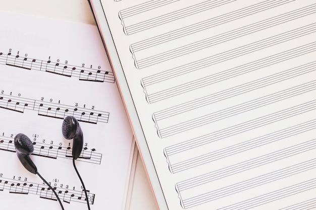 Fone de ouvido preto na nota musical com tablet digital